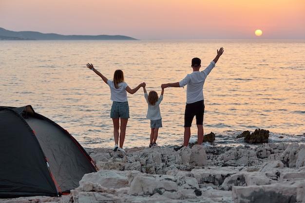 岩のビーチで両手を広げて立っている甘い若い家族の背面図です。
