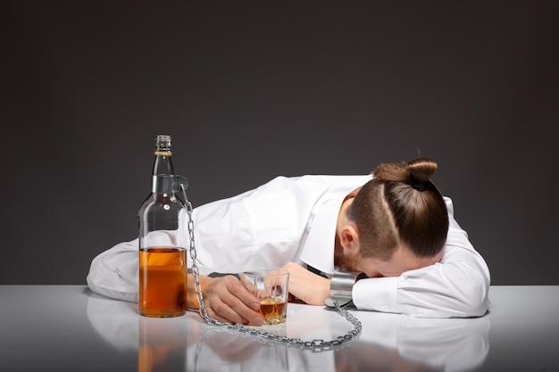 疲れている若いビジネスマンを飲みます