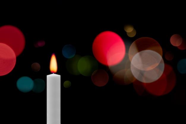 さまざまな色のボケ味の光で暗闇の中でロマンチックなキャンドルライト。