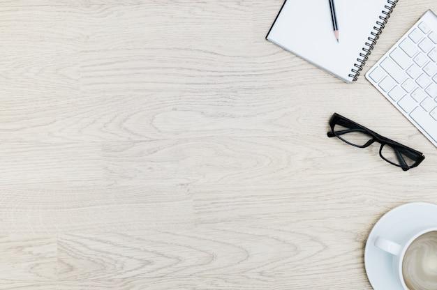 メモ帳、マウス、キーボード、コーヒーカップ、黒眼鏡のオフィステーブル。ビジネスフラットレイアウトデザインで上からの眺め
