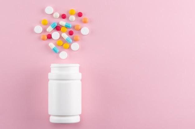 コピースペースとピンクのペットボトルから注ぐ薬の様々な錠剤やカプセルテキストまたはデザインの追加