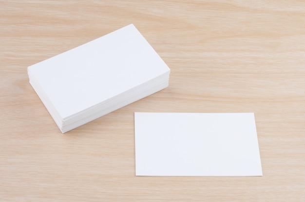 木製のテーブルの上の空白の白い名刺紙