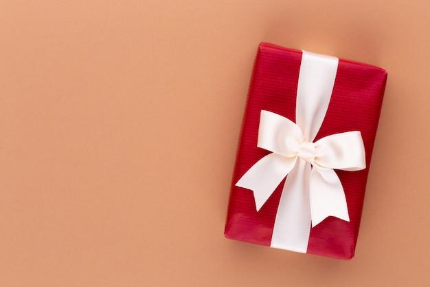 色卓上にリボン付きのクリスマスギフトボックス