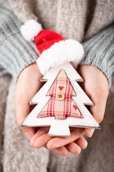 冬のコンセプトクリスマスの装飾を保持している若い手。クリスマスの装飾のアイデア。女性、ゴールドのボケ味を持つ背景の手の中のクリスマスの装飾。