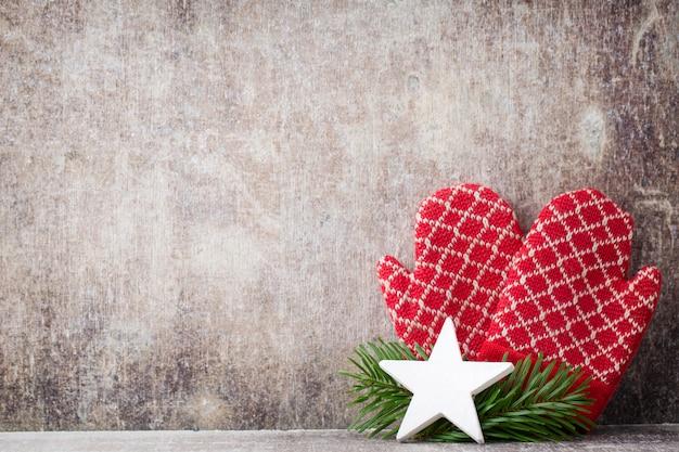 クリスマスの木製の背景に赤いミトンの手袋。