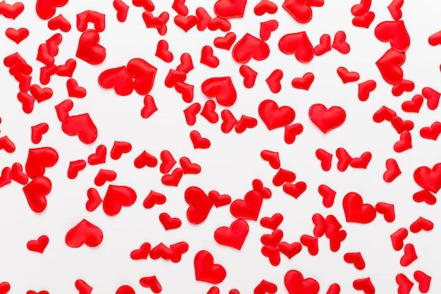 バレンタインデーの背景の白い木製の背景に赤いハート。