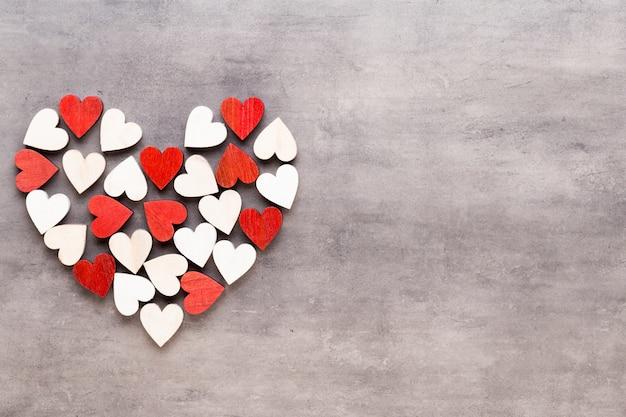幸せなバレンタインデーの背景。灰色の背景に小さな心を持つ。