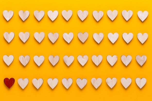 幸せなバレンタインデーの背景。黄色の背景に小さな色の心。