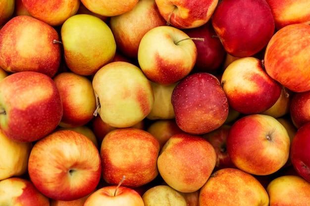 市場に出回っている多くのジューシーな明るいリンゴ。上からの眺め。閉じる。壁。