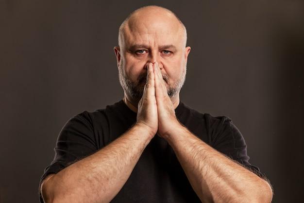 ハゲ男は祈りの中で彼の顔で手を組んだ。信仰と希望。暗い壁。