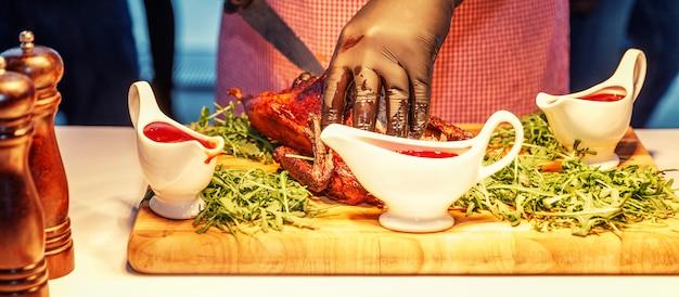 Руки официанта в черных перчатках за фуршетом режущего аппетитного гуся с жареной корочкой. крупный план. панорама.