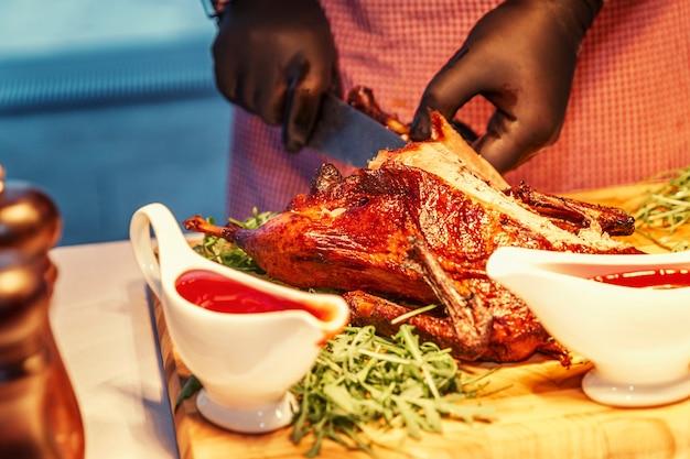 Руки официанта в черных перчатках за фуршетом режущего аппетитного гуся с жареной корочкой. крупный план.