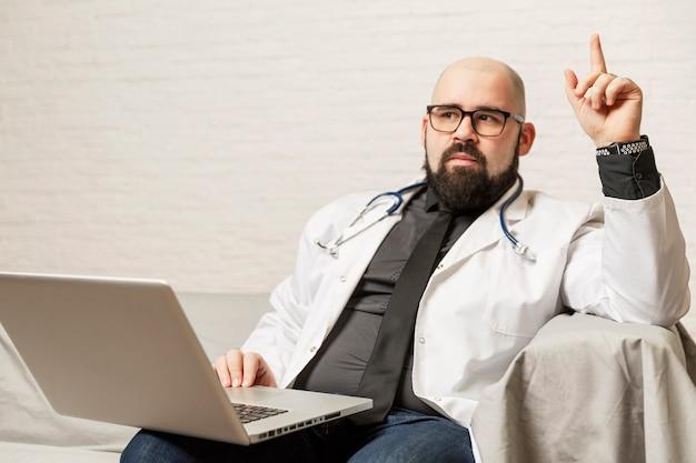 白いコートを着た男性医師がラップトップでソファに座っています。ブログとコーチング。