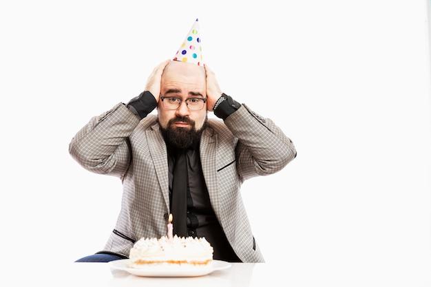 道化師の帽子をかぶった男がキャンドルの前でケーキの前に座っています。悲しい誕生日。白い壁。