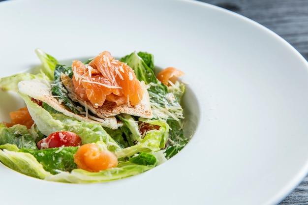 Салат цезарь с рыбой в тарелке на столе из пряничного дерева. крупный план.