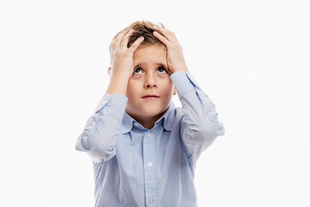 Мальчик школьного возраста в синей рубашке держит голову в руках. усталость и апатия. изолированные на белом