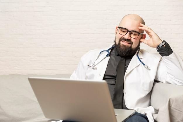 男性医師はソファーに座っているし、ラップトップの前で動作します。伝染病の間の遠隔作業、オンライン相談。