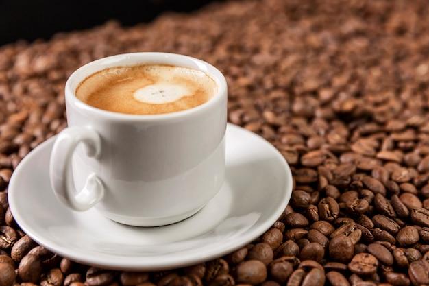 Белая чашка с ароматным кофе стоит на разбросанных зернах.