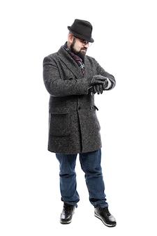 コートと帽子をかぶったスタイリッシュな男が彼の時計を見ています。