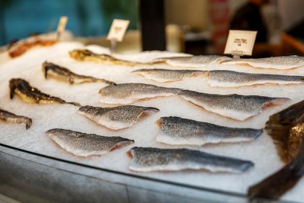 レストランのウィンドウで氷の上で様々な新鮮な魚の切り身。新鮮なキャッチ。