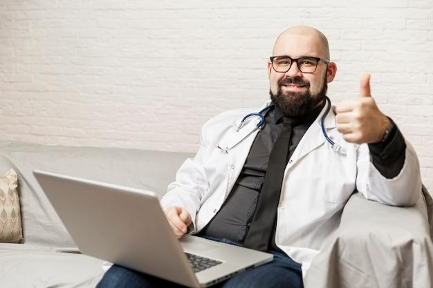 ソファの上のラップトップで眼鏡をかけた白衣のハゲの男性医師が座っています。オンライン相談。コロナウイルスのパンデミック時の検疫。