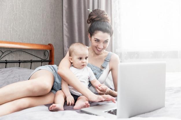 Счастливая улыбающаяся молодая мама с маленьким ребенком работает из дома, сидя на кровати.