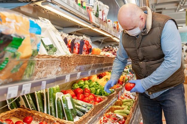 医療マスクのハゲ男がスーパーで野菜を選びます。菜食主義と健康的なライフスタイル。コロナウイルス大流行時の注意事項。