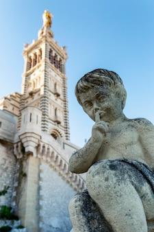 Статуя ангела в виде мальчика на фоне собора нотр-дам в марселе. вертикальная.