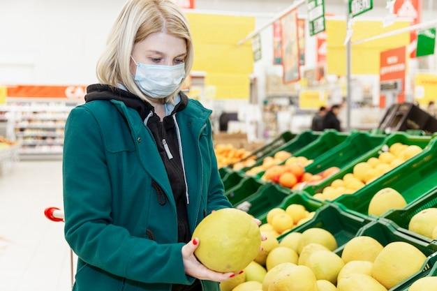 医療マスクのブロンドの女性はスーパーで果物を選択します。コロナウイルスのパンデミック時の注意事項。