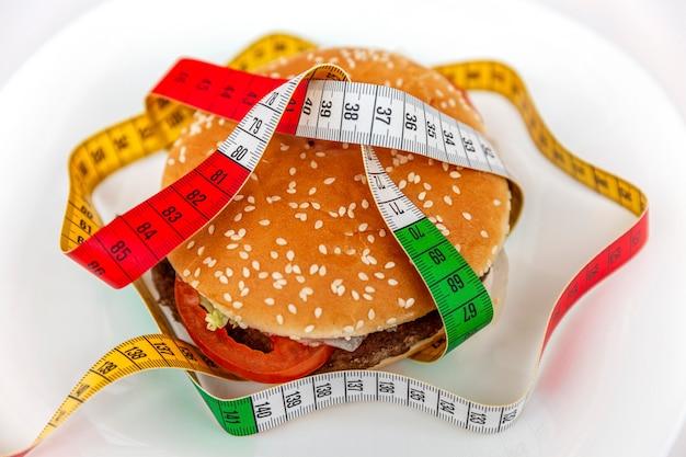 マルチカラーのメジャーテープが巻きついた皿の上に座っているチーズバーガー。太るのを恐れて健康的なライフスタイルに固執することの微妙な注意。