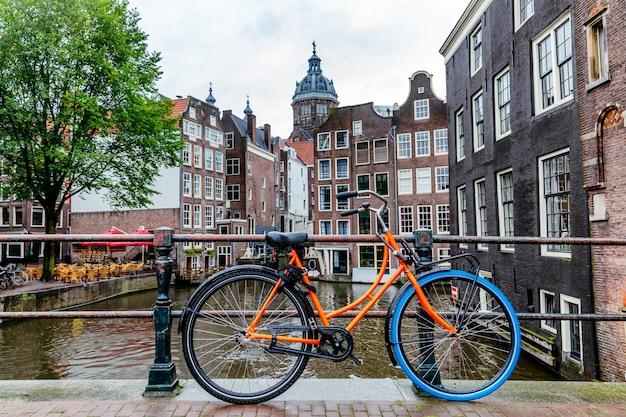 Прекрасный вид на канал в амстердаме. дома на воде, велосипеды с цветами нм моста. отличный городской пейзаж.