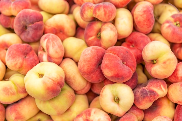 Спелые сочные персики в коробке в супермаркете.