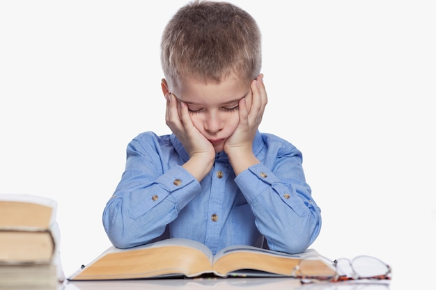 Школьник делает домашнее задание за столом. грусть и усталость от учебы. изолированный над белизной.