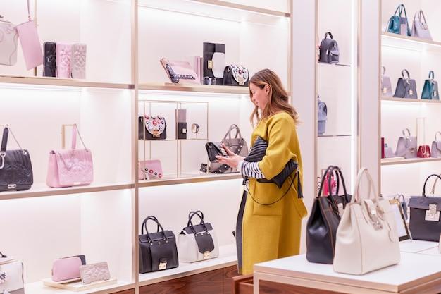 明るいコートを着た若い女性が店でバッグを選びます。ファッションアクセサリーの豊富な品揃え。