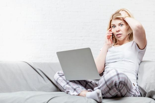 Молодая женщина в пижаме с изумленными эмоциями на лице сидит на сером диване с ноутбуком на коленях. удаленная работа во время пандемии коронавируса. паника и финансовый кризис. пространство для текста.