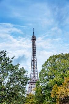 明るく青い曇り空を背景に緑豊かな木々に囲まれたエッフェル塔。垂直。
