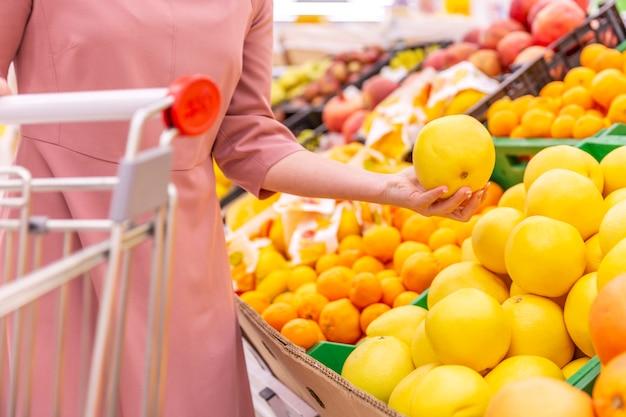若い女性がスーパーマーケットでグレープフルーツを選択します。