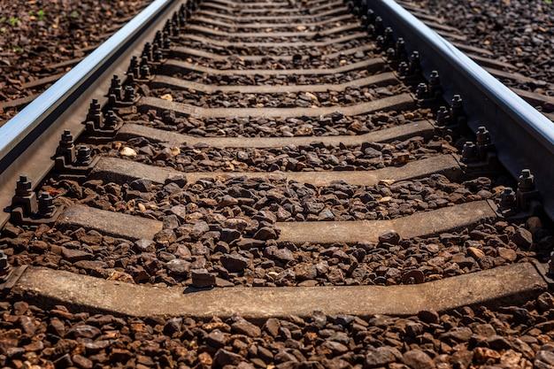Железнодорожные пути. металлические рельсы и шпалы. крупный план. путешествия и туризм.