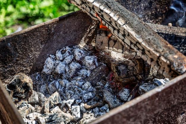 Угли, горящие в жаровне. пикник на природе. крупный план.