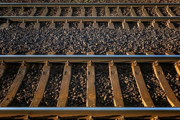 Железнодорожные пути. металлические рельсы и шпалы. крупный план. путешествия и туризм. стены. пространство для текста.