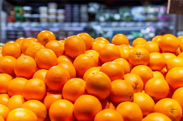 スーパーのカウンターで熟したオレンジ。ビタミンと健康的な食事。閉じる。