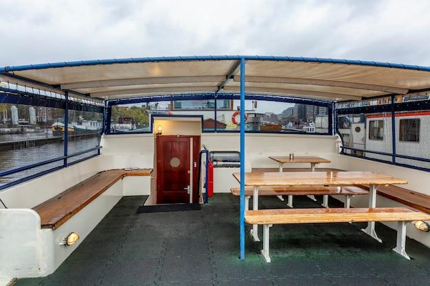 Столы со скамейками на корме гостиничного корабля в амстердаме. место для отдыха пассажиров клиентов.