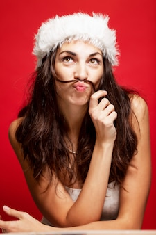 サンタクロースの帽子笑顔で美しい若い女性。クリスマスの物語。はがき。垂直。赤 。
