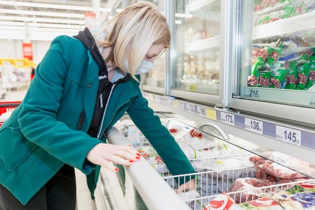 医療用マスクを着た金髪の女性がスーパーの冷凍部門で商品を選びます。コロナウイルスのパンデミック時の注意事項。