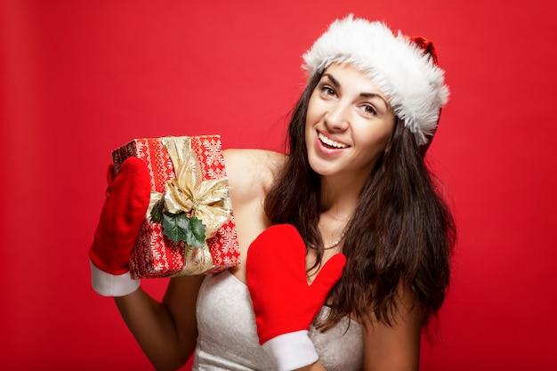 Красивая молодая женщина в шапке санта-клауса и варежки с подарком в руках улыбается. рождественская сказка. открытка. вертикальная. красный