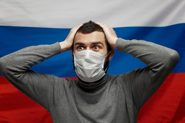 Молодой человек в медицинской маске в панике держит руки за голову на фоне российского флага. крупный план. день независимости на фоне пандемии коронавируса.