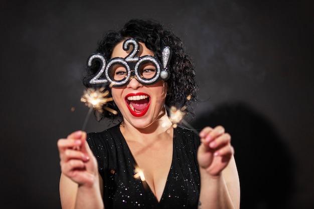 花火を持つ若い笑う女性。巻き毛のブルネット。新年のお祝い。