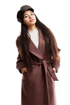 キャップと茶色のコートを着た若い女の子の笑顔。スタイリッシュな秋のルック。白い背景で隔離されました。垂直。