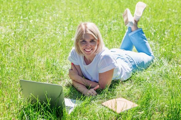若いブロンドの女性はノートパソコンで芝生の上の公園にあります。ブログ、教育、遠隔作業。