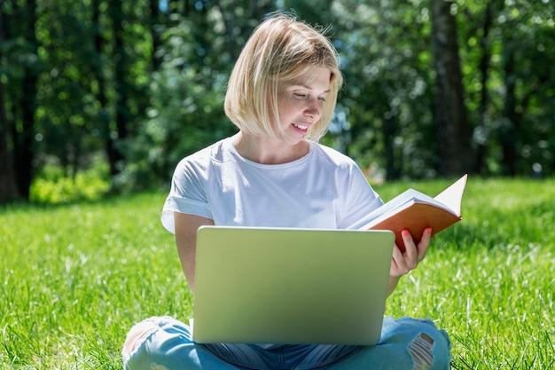 パソコンで草の上の公園に座っている若いブロンドの女性。ブログ、教育、遠隔作業。